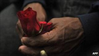 A relative of a civil-conflict victim holds a rose on 2 August 2011 in Guatemala City