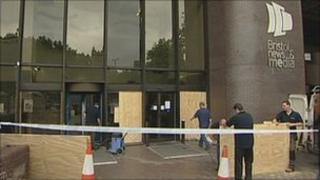 Workmen boarding up broken windows at Evening Post building