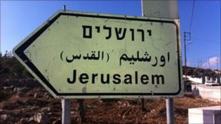 Sign pointing to Jerusalem in Hebrew, Arabic and English