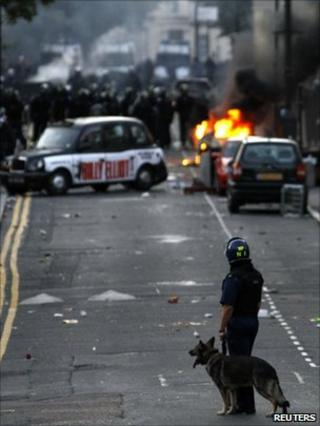 A police dog handler stands behind officers in riot gear blocking a road near a burning car on a street in Hackney
