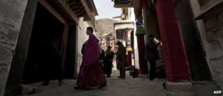 Tibetan monk walks past pilgrims at the Labrang monastery in Xiahe, Gansu province, file image