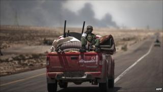 Libyan rebels drive on an armed pick-up truck towards the frontline on August 15, 2011 on the outskirt of Brega