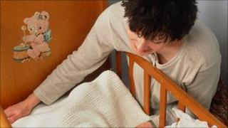 Mother putting baby in cot