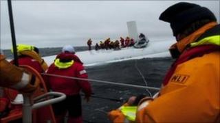 A number of the crew huddled together on the hull of the boat