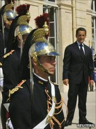 French President Nicolas Sarkozy stands beside guards outside the Elysee Palace in Paris, 16 August