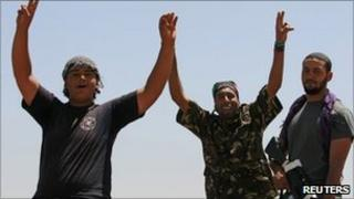 Libyan rebel fighters celebrate as they drive into the coastal city of Zawiya on Monday