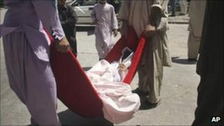 Afghans carry a victim of a roadside bomb in to a hospital in Herat - Aug. 18, 2011