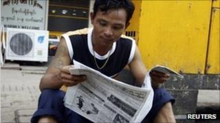 A man reads a newspaper in Rangoon on 17 August 2011