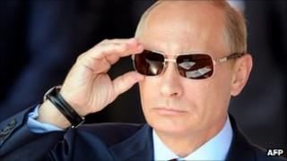 Russian Prime Minister Vladimir Putin adjusts his sunglasses at a Moscow air show, 17 August