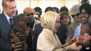 Turkish Prime Minister Recep Tayyip Erdogan (left) and his wife Emine Erdogan hold children from southern Somalia during a visit to a camp for internally displaced people in Mogadishu - 19 August 2011