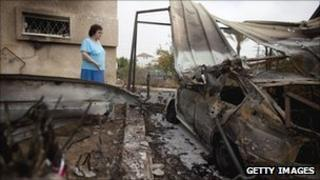 An Israeli woman in Beersheba looks at a car that was hit by a rocket fired by Palestinian militants from the Gaza Strip on Saturday