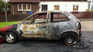 Burnt-out car in front of house in Derry