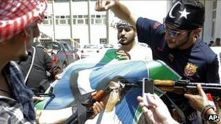 Libyan rebel fighters from Tripoli brigade deface a portrait of Libyan leader Muammar Gaddafi in Tripoli, Libya, Monday, 22 Aug 2011