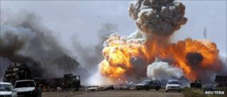 Vehicles belonging to forces loyal to Libyan leader Muammar Gaddafi explode after an air strike by coalition forces, along a road between Benghazi and Ajdabiya in this March 20, 2011 file photo