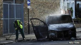 A street cleaner sweeps up around a smouldering van set alight during riots in Hackney in London