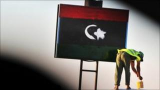 Man paints Libyan flag on a checkpoint
