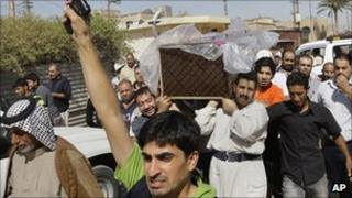 Friends and relatives mourn as they carry the coffin of Ali Saleh, 25, during his funeral procession in Baghdad, Iraq