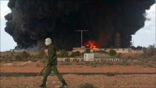 A rebel walking past a burning oil terminal