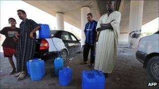 People buy petrol under a motorway bridge in the Libyan capital Tripoli.