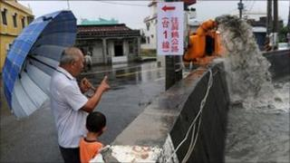 "A man shows his grandson a water pump (R) extracting overflowing water caused by rain brought by Typhoon Nanmadol in Linbian in Taiwan""s southern Pingtung county on August 29, 2011."