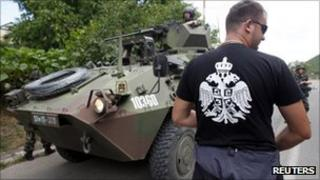 A Kosovo Serb stands in front of a K-For peacekeepers patrol near Zvecan, 30 July