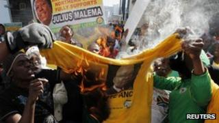Julius Malema's supporters burn a t-shirt with President Zuma's face, Johannesburg, South Africa (30 Aug 2011)