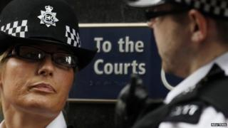 Two police officers stand outside a court