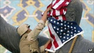 US marine covers the face of Saddam Hussein with an American flag