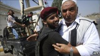 A rebel fighter and a Libyan man embracing