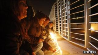People light candles outside TVN national television in Santiago, 3 September 2011