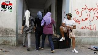"""Libyan youths stroll in the streets next to graffiti reading """"Free Libya, The rebels From The Old City"""" in Tripoli, Libya, on Saturday"""