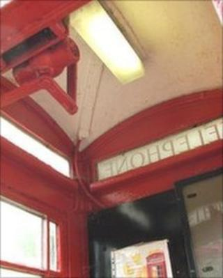 The light shines inside the red phone box at Arlingham, Gloucestershire