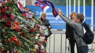 A fan throws a Lokomotiv Yaroslavl scarf onto a pile of flowers