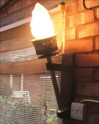 Olympic torch being used as a wall light