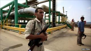 An anti-Gaddafi fighter stands guard at the Mellitah Oil and Gas complex