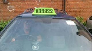 A private hire taxi with roof sign