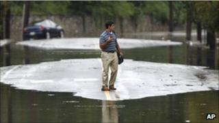 A man stands between flooded ground in Philadelphia, PA on 8 September 2011