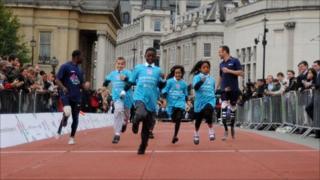 Oscar Pistorius (r) and Jerome Singleton (l) race with children in Trafalgar Square