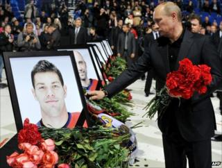 Russian Prime Minister Vladimir Putin lays flowers by the coffins of players in Yaroslavl, 10 September
