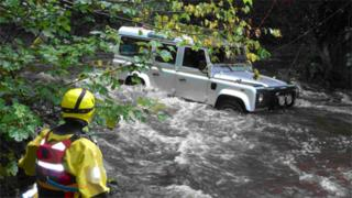 Firefighter surveying the secured vehicle following the rescue of the occupants