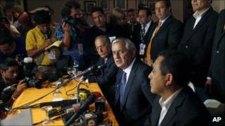 Otto Perez Molina (centre) talks to reporters on 12 September