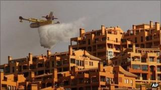 A firefighting plane dumps waters on homes in Marbella, Spain (12 Sept 2011)
