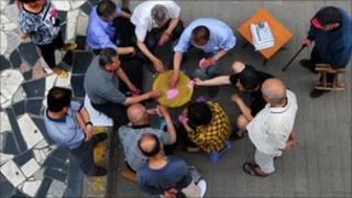 Retired elderly people play a game of cards on a Beijing sidewalk