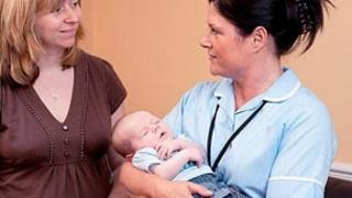 Midwife with mother and baby