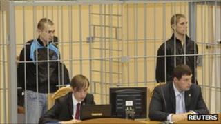 Dmitry Konovalov (L) and Vladislav Kovalyov stand inside a court cage in Minsk, 15 September