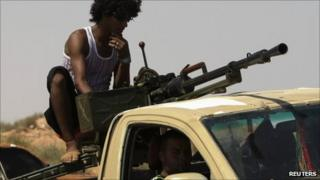Anti-Gaddafi fighters drive their pickup with a heavy machine gun, around 65km (40 miles) east of Sirte
