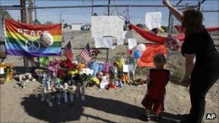 A memorial for crash victims against a airfield gate