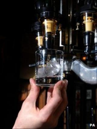 Bartender measuring a shot of Bells Whisky into a glass