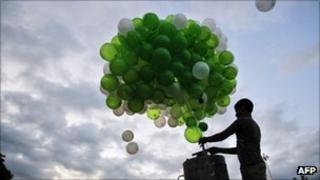 Boy releases green balloons into the sky