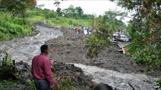 A man watches a river of mud in Santa Cruz Barillas